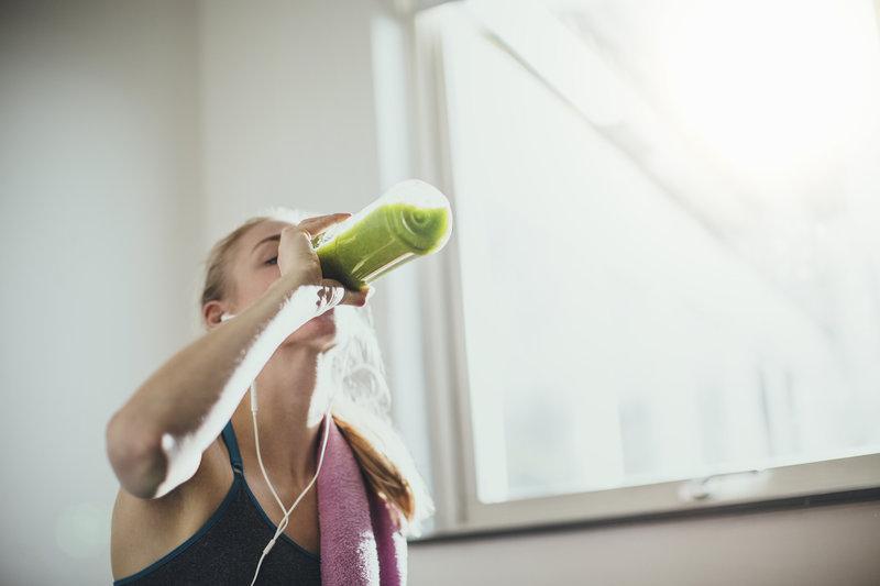 Eine junge Frau trinkt einen grünen Smoothie nach dem Training