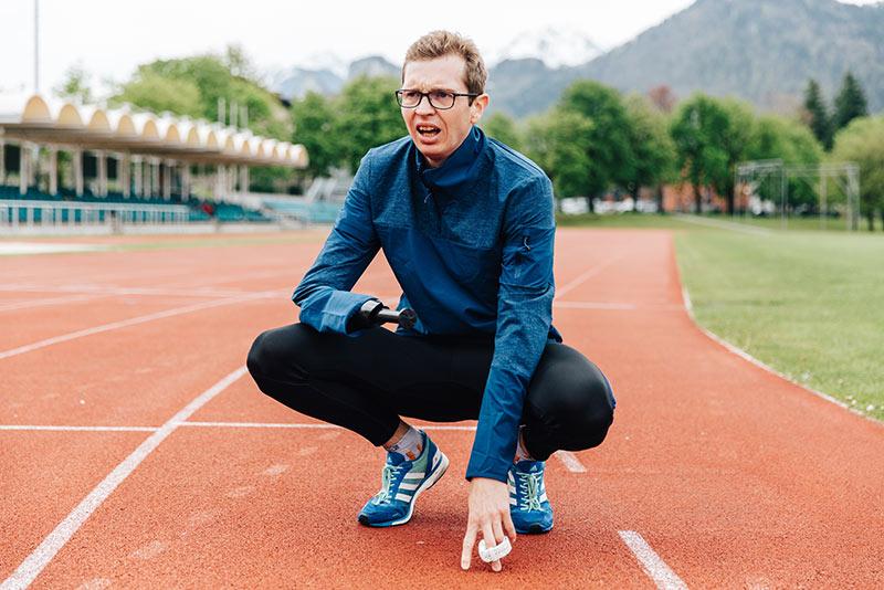 Ein Mann hockt nach dem Lauf auf dem Boden