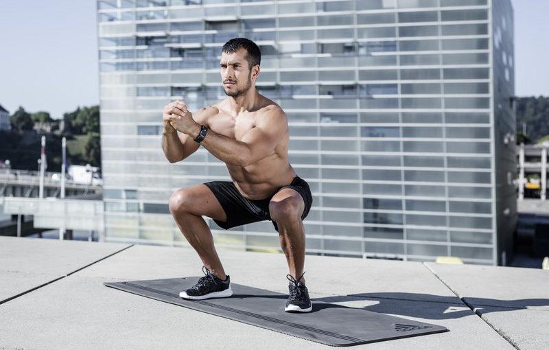 Shirtless man squatting