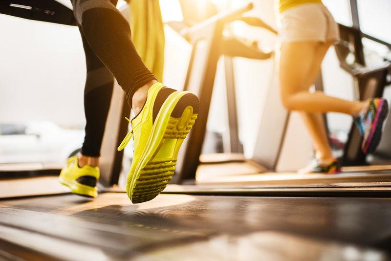 Zwei nicht erkennbare Sportler beim Workout am Laufband im Fitnessstudio
