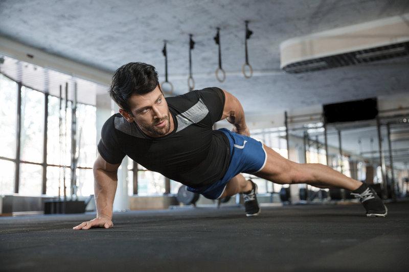 Athletischer junger Mann macht einarmige Liegestütze im Fitnessstudio