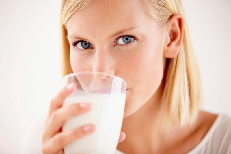 Huebsche junge Frau trinkt ein Glas Milch.