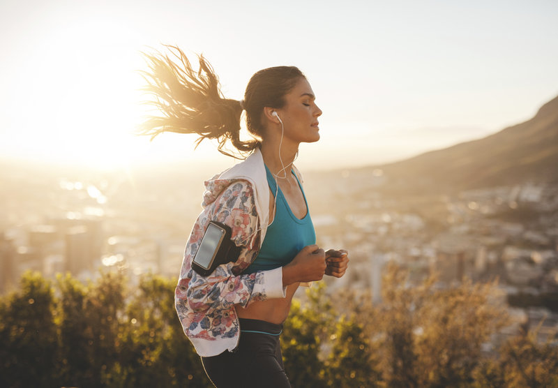 Young woman is running and enjoys her music playlist.