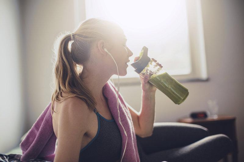 Eine Frau die einen grünen Smoothy trinkt.