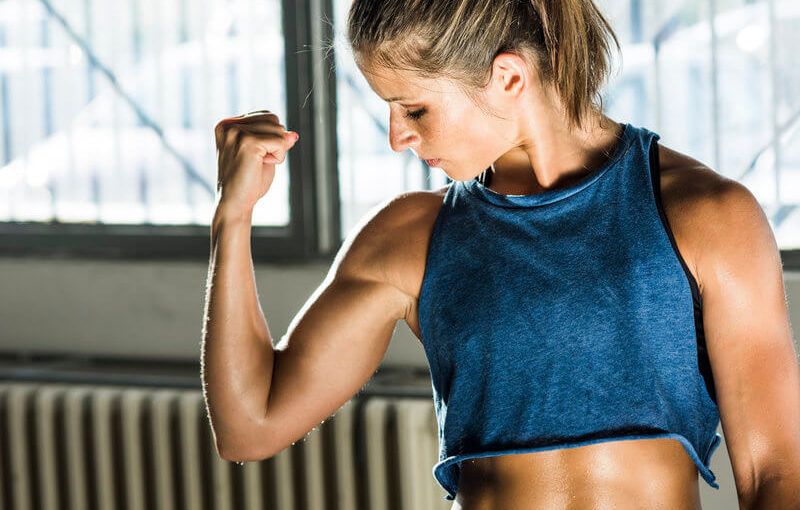 Athletic woman flexing her biceps.