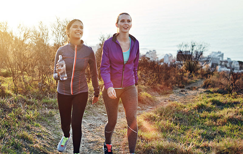 Two friends walking outside with the Runtastic App.