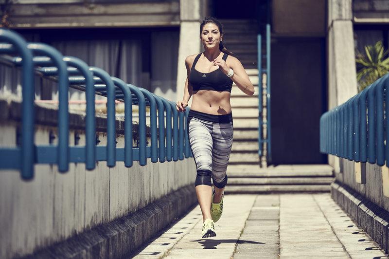 Junge Frau beim Laufen fuer ihre Halbmarathon Vorbereitung.