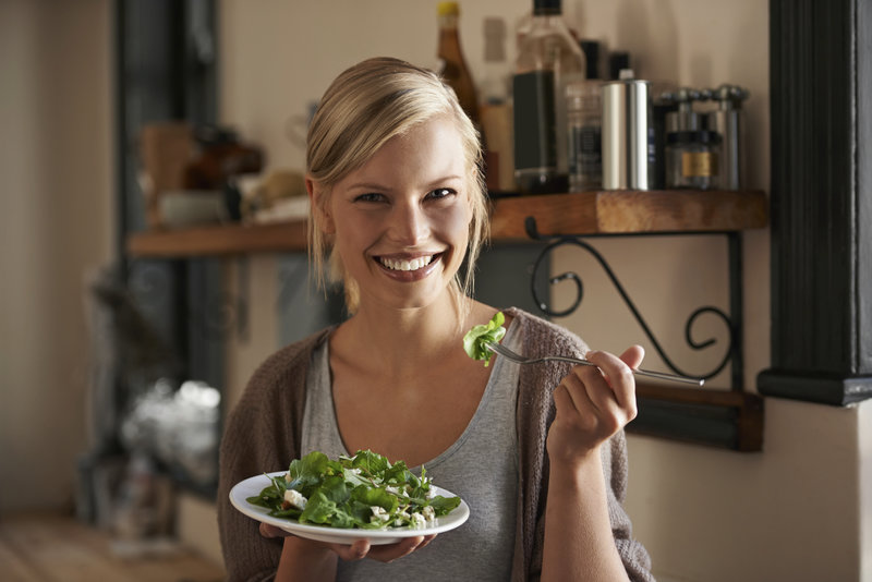 Jeune femme qui mange une salade