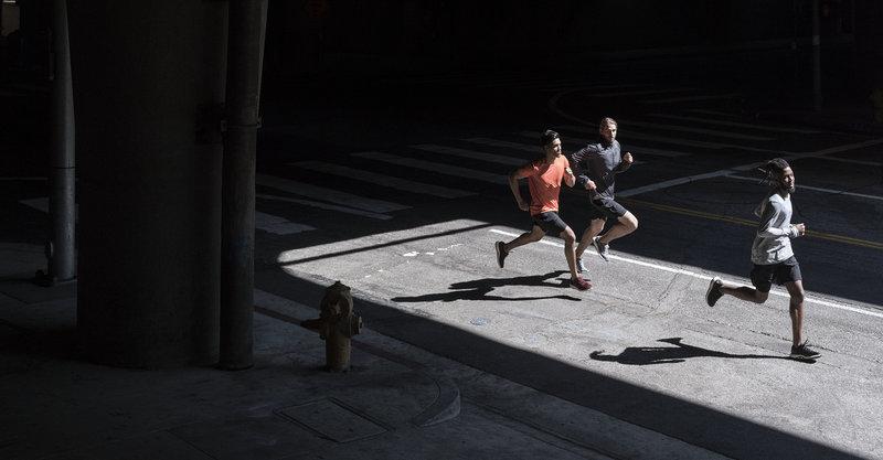 Drei Männer laufen im Freien