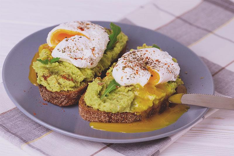 Zwei Scheiben Brot mit Avocado und pochierten Eiern auf einem Teller