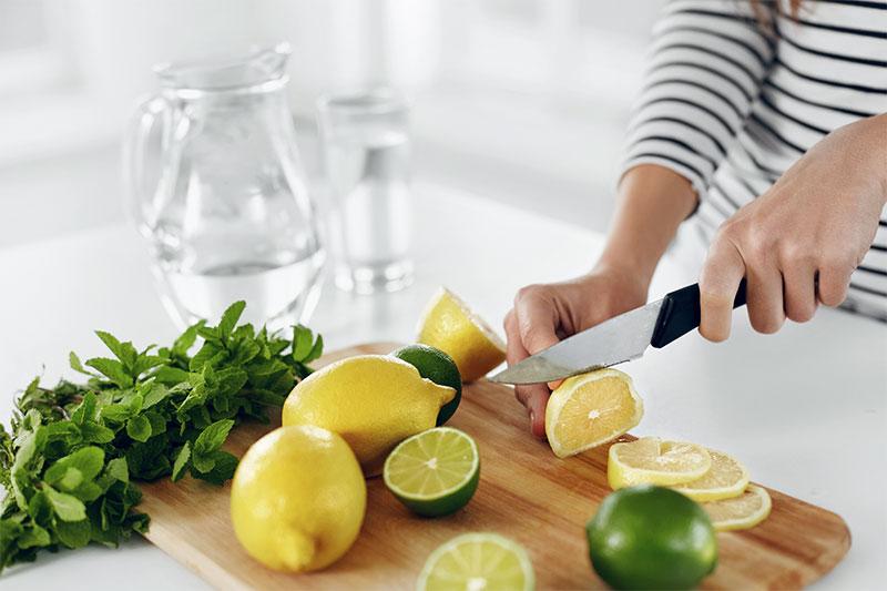 Eine Frau schneiden Zitronen und Limetten auf einem Holzbrett
