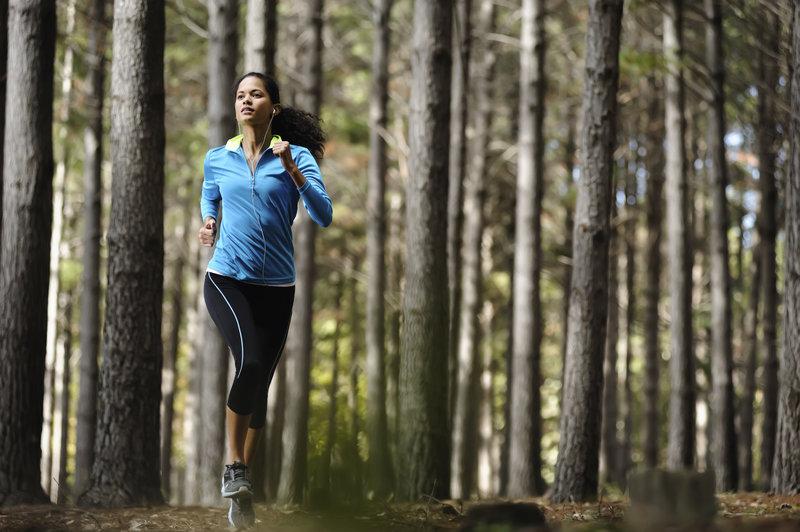 Junge Frau trainiert für einen Crosslauf im Wald.