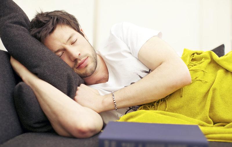 Junger Mann schlaeft nach einem anstrengenden Arbeitstag tief und fest auf der Couch.