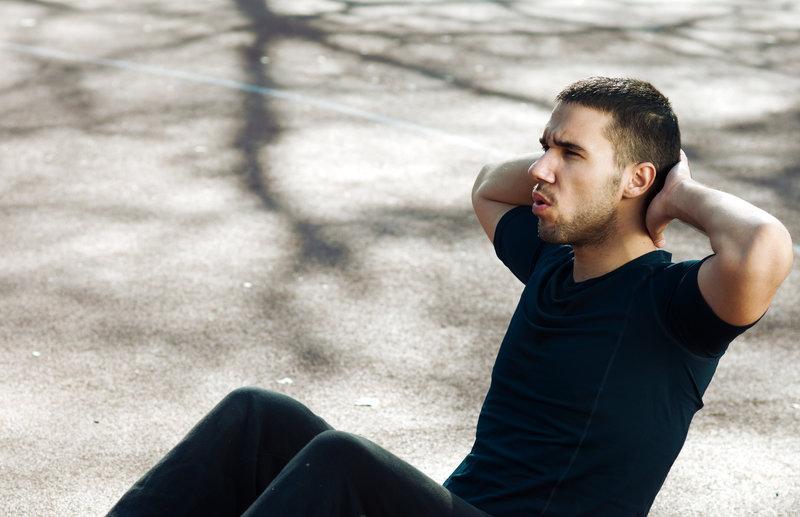Junger Mann macht Sit-ups im Freien.