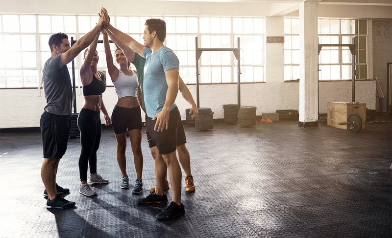 Group of friends celebrate with a high five after their workout.