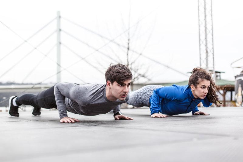 Ein junges Paar macht Push-ups im Freien.