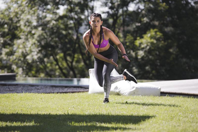 Junge Frau macht ein Training mit dem eigenen Koerpergewicht im Freien.