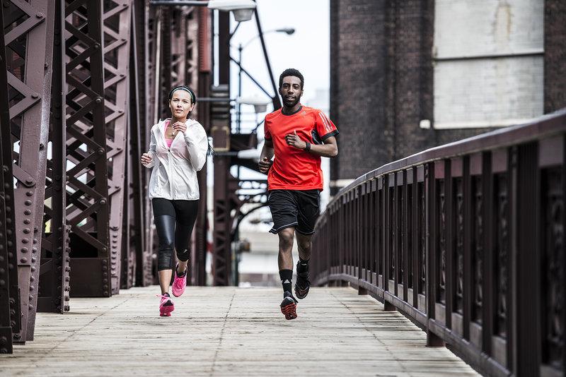 Man and woman running on a bridge
