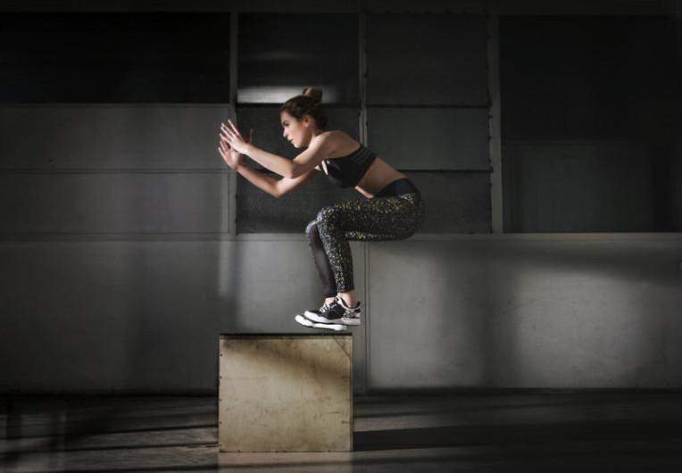 Jeune femme qui saute sur un socle.