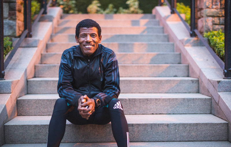 A man sitting on the stairs in running gear and smiling into the camera