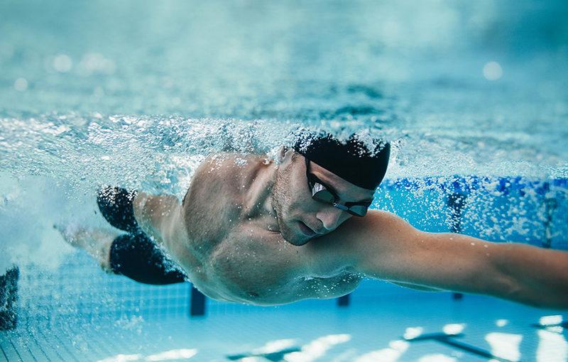 Ein Mann krault im Schwimmbad