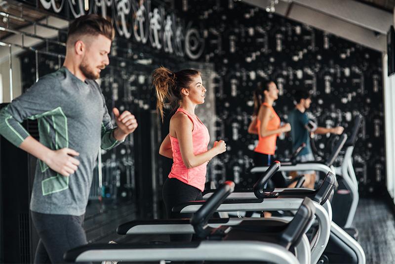 Ein paar Leute laufen im Fitnessstudio am Laufband