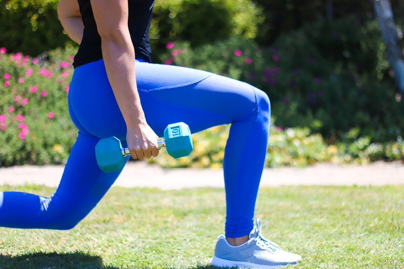 Close up of woman doing a lunge with a dumbbell in her hands.