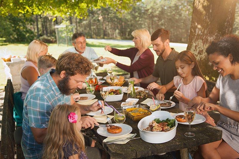 Eine Familie die im Garten an einem reich gedeckten Tisch sitzt.
