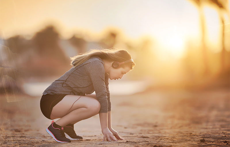 Young woman stretching before her earliy morning run.