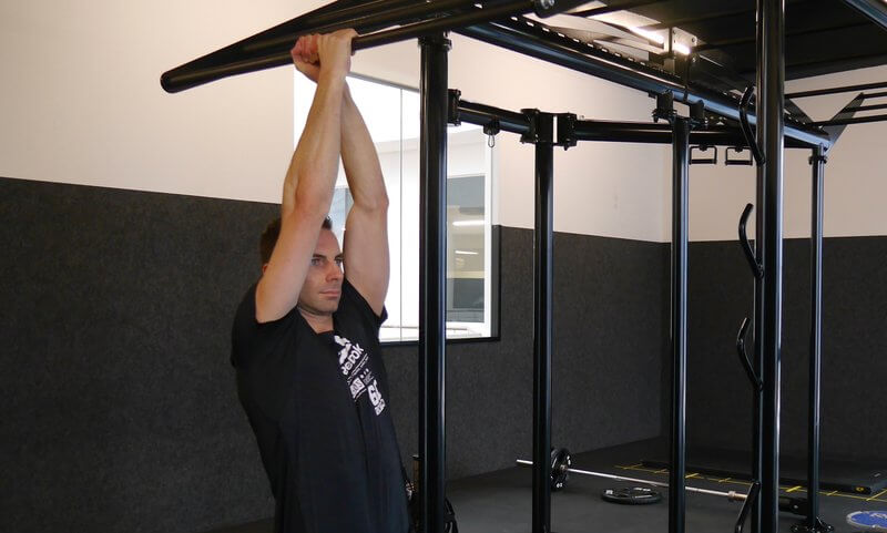 Athletic man doing Commando Chin-ups.