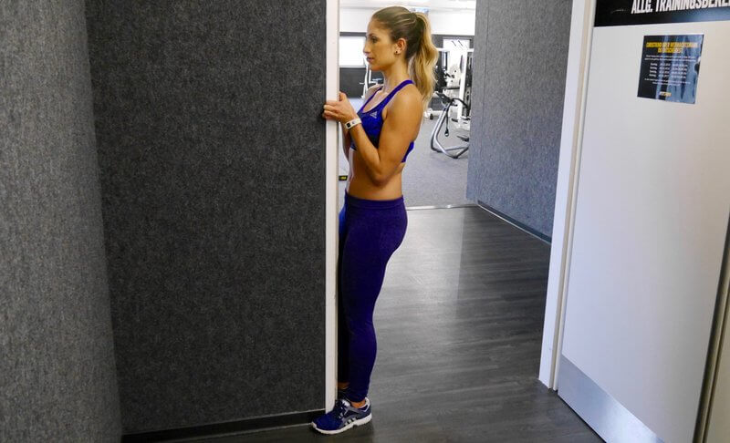 Athletic woman doing Doorway curls.