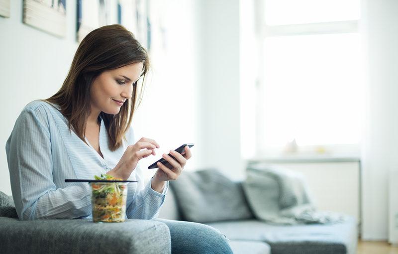 Eine Frau gibt ihr Mittagessen auf der Runtastic Balance App ein