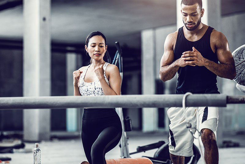 A man and a woman working out in the gym