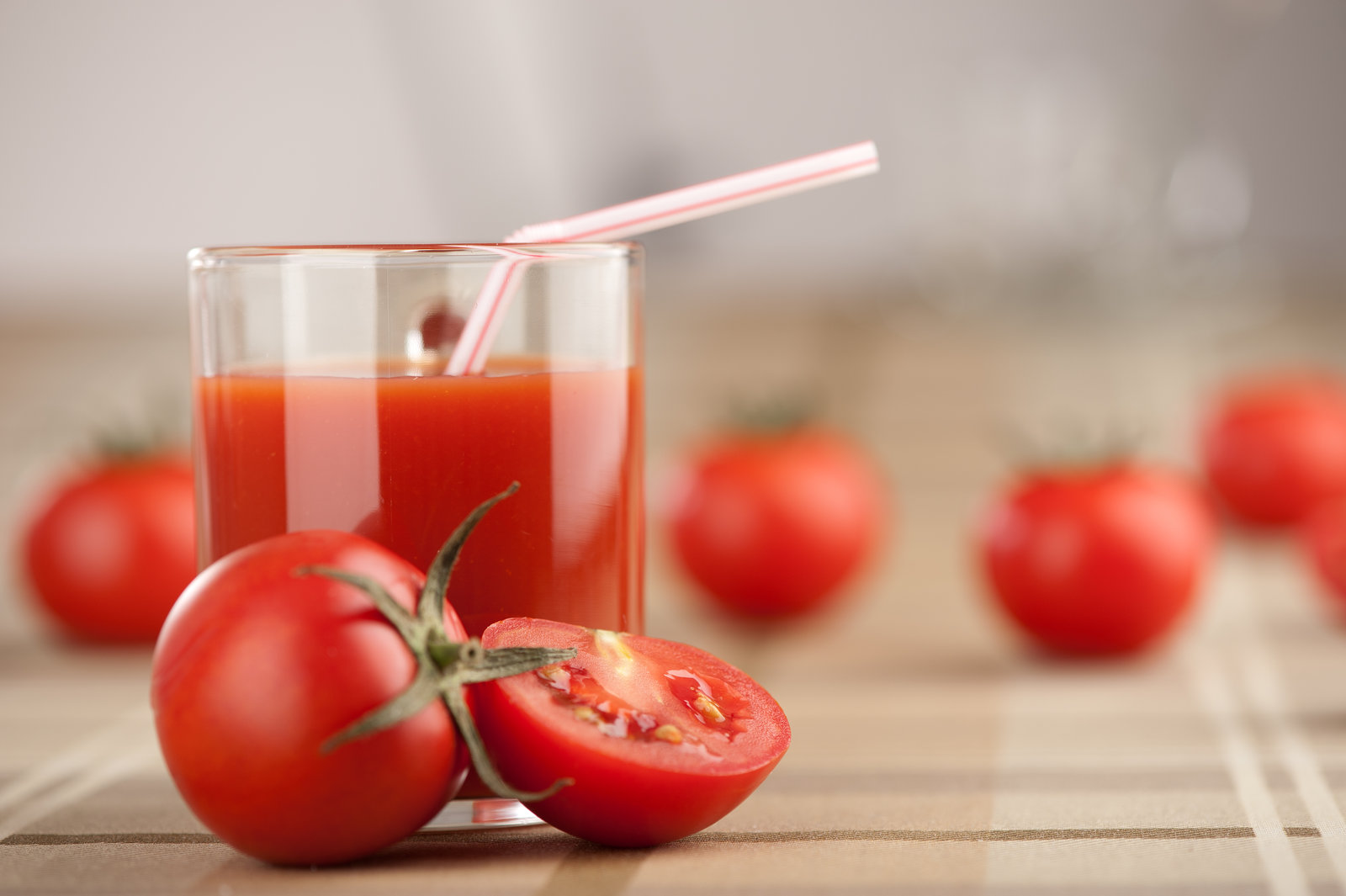 Vaso de zumo de tomate, con tomates alrededor