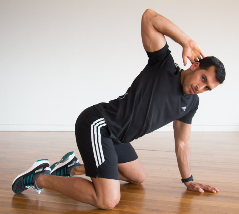 Young man doing a mobilisation exercise for his back in the all fours position.