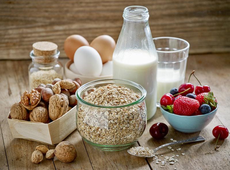 Nuesse, Eier, Haferflocken und Milch auf einem Holztisch.