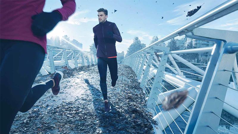 Ein Mann läuft bei Wind auf einer Brücke