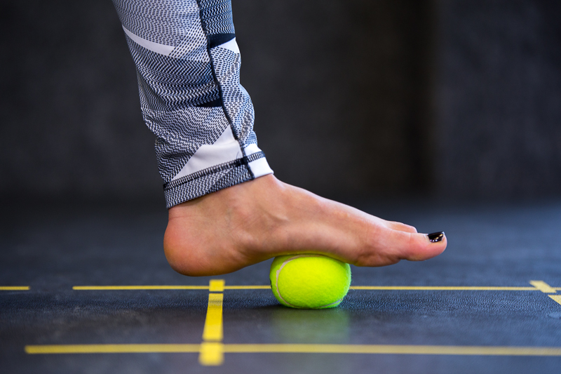 A woman is rolling her foot on a tennis ball