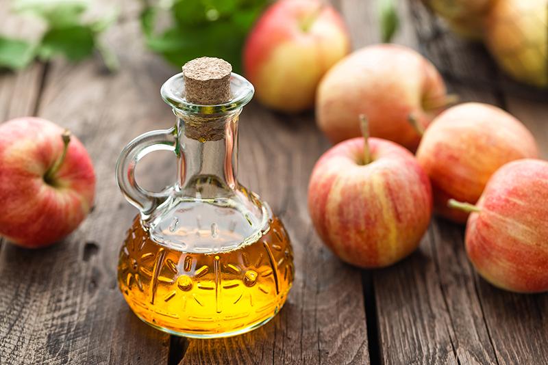 Eine Flasche Apfelessig auf einem Holztisch