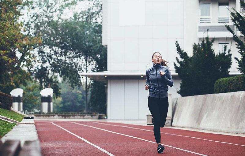 Eine Frau läuft auf einer Laufbahn