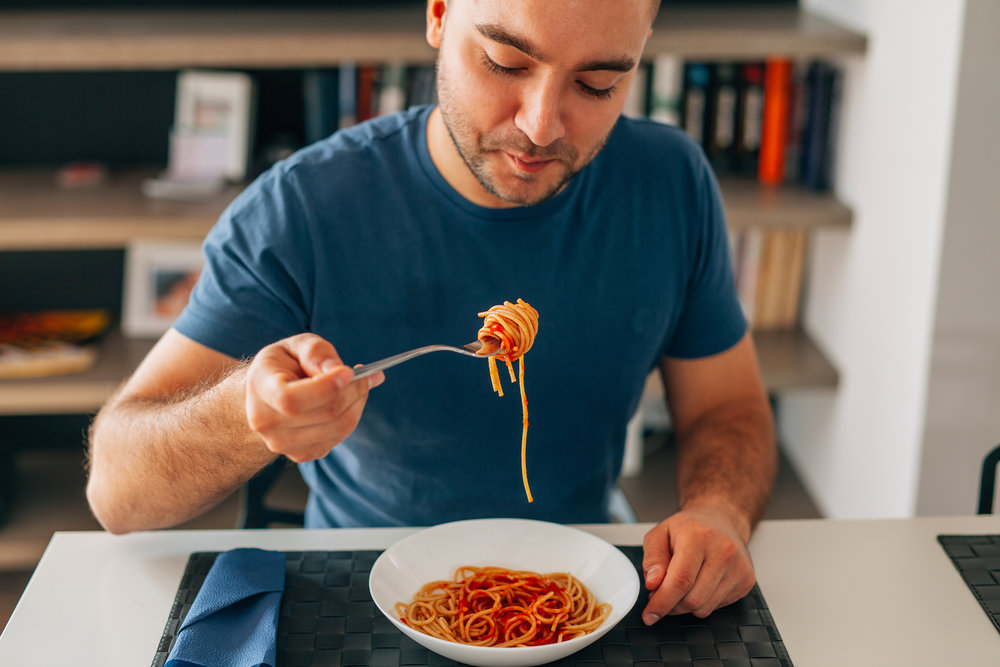 Young man eating spaghetti bolognese.