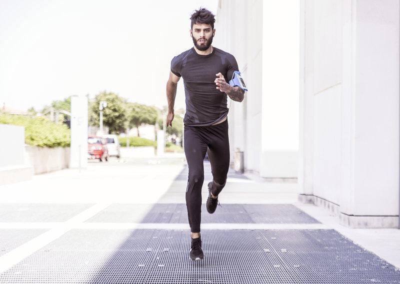 Ein Mann der auf dem Gehsteig läuft.