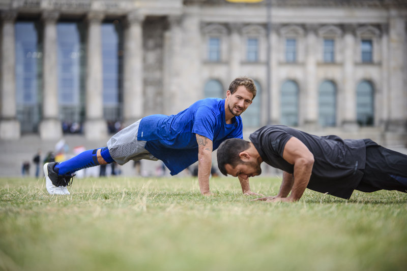 Two friends doing a bodyweight training with Runtastic Results outside.