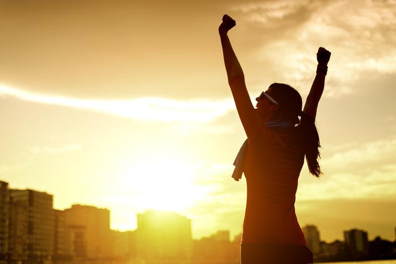 Junge Frau streckt ihre Arme dem Sonnenuntergang entgegen.