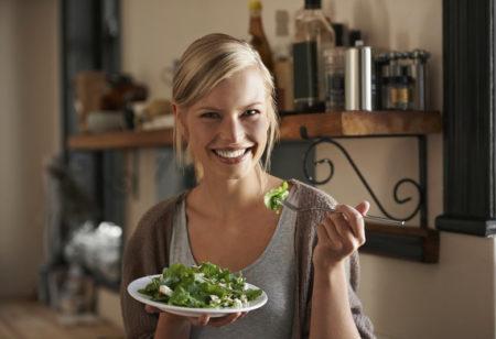 Eine Frau die fröhlich ihren Salat isst.