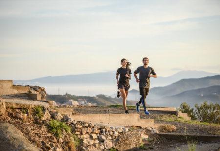Zwei Freunde beim gemeinsamen Laufen auf einer Bergstraße.