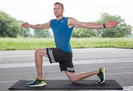 Athletic man doing a Lunge and Twist.