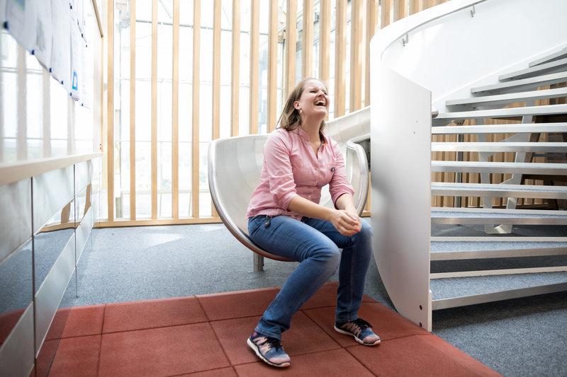 Junge Frau sitzt auf einer Rutsche und lacht