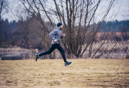 Young man is running outdoors on a cold winter day.