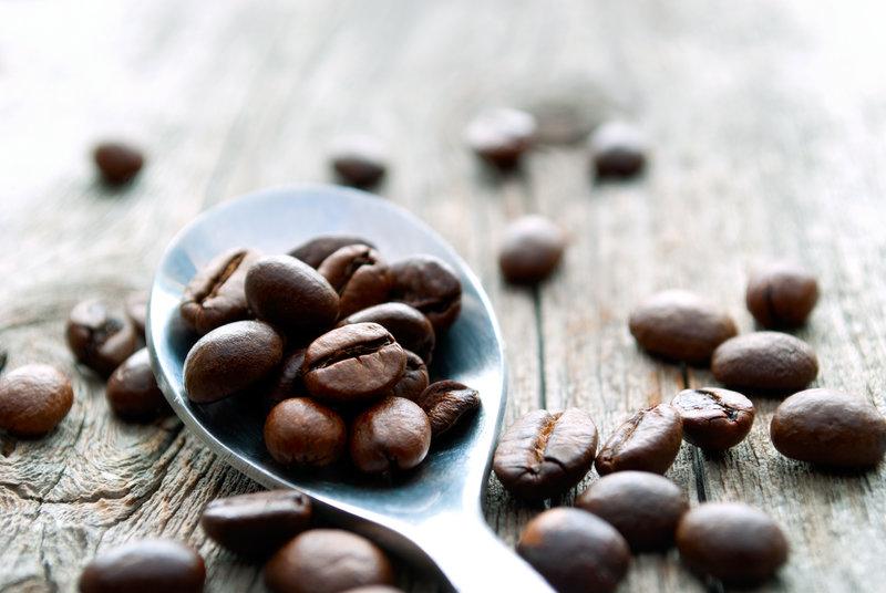 Une cuillère remplie de grains de café.